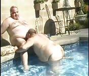 Tres pibes gorditos junto a la piscina