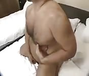 Hairy Asian man masturbating in a hotel room