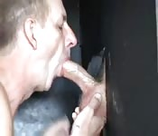 Mature gay man sucking a huge cock through a glory hole