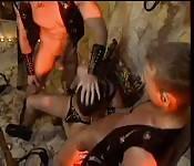 Leather-clad sex slave having threeway fun