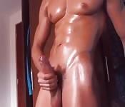 Rapaz bonito e com óleo no corpo brincando com o pau enorme