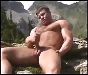 Homem musculoso brincando com seu pau enorme