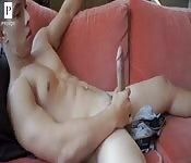 Muscled young stud masturbating on his sofa