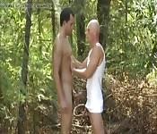 Un calvo se la chupa a su amigo moreno en el bosque