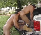 Men fuck on top of a car